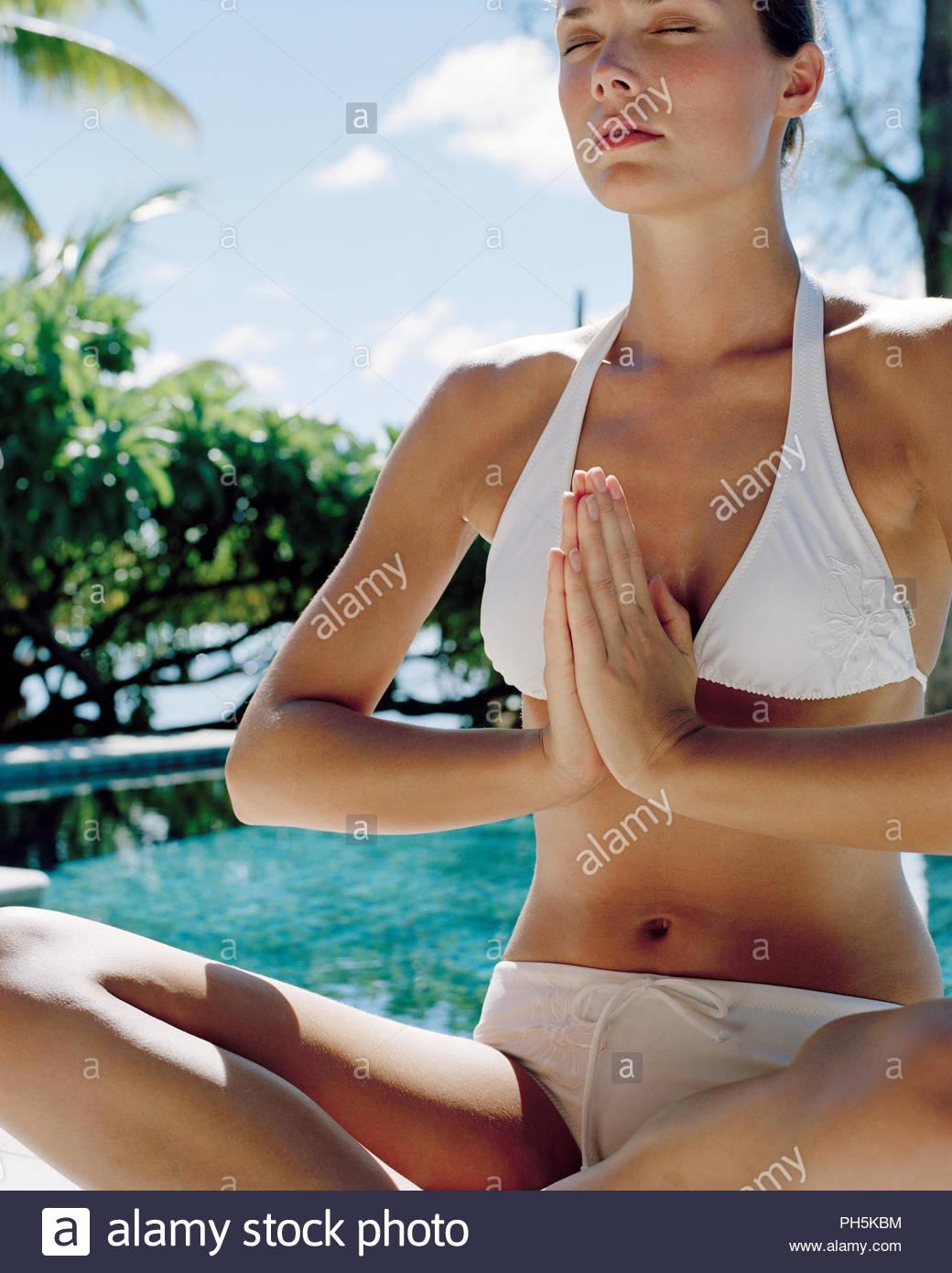 Woman meditating beside swimming pool. - Stock Image