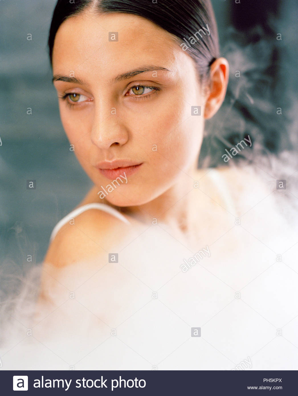 Young woman surrounded by steam - Stock Image