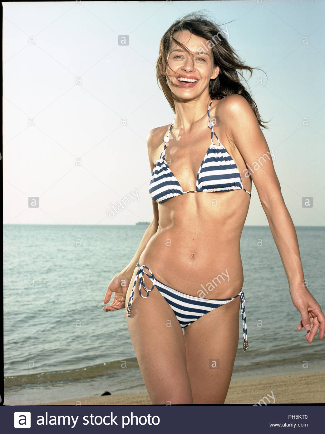 Woman in striped bikini at beach - Stock Image