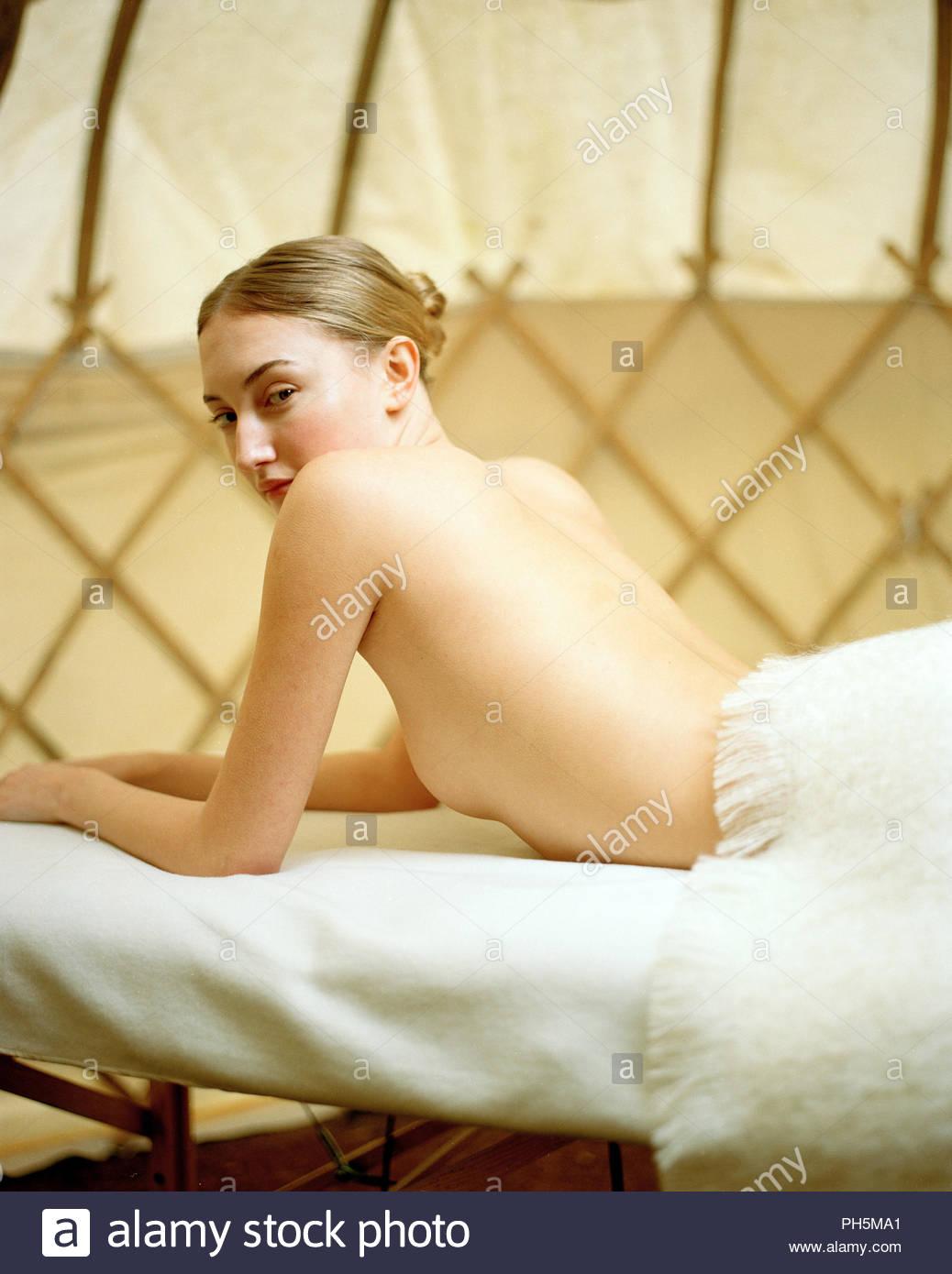 Shirtless young woman lying on massage table - Stock Image