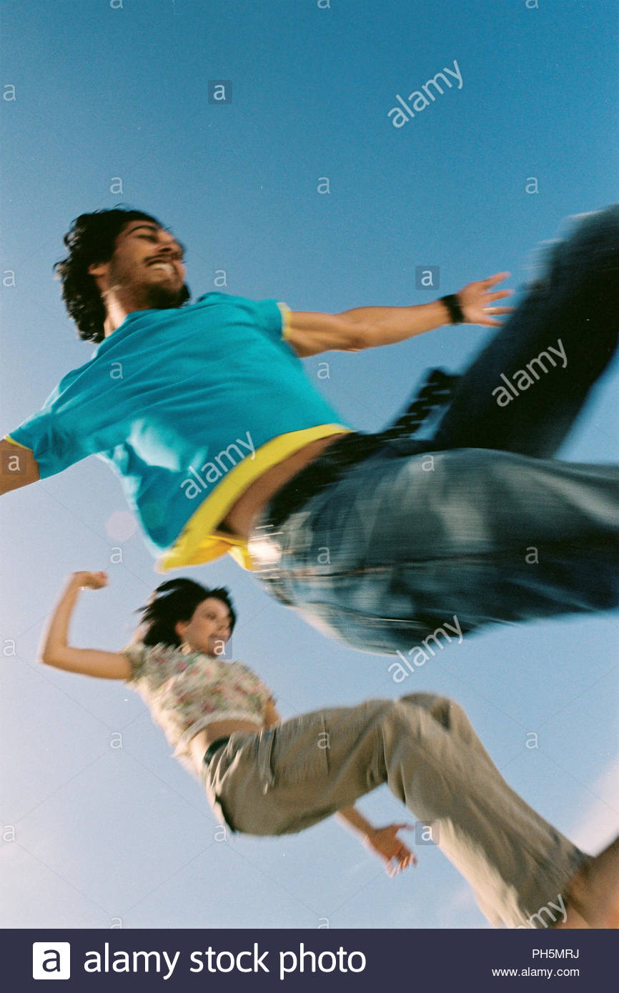 Couple jumping together - Stock Image