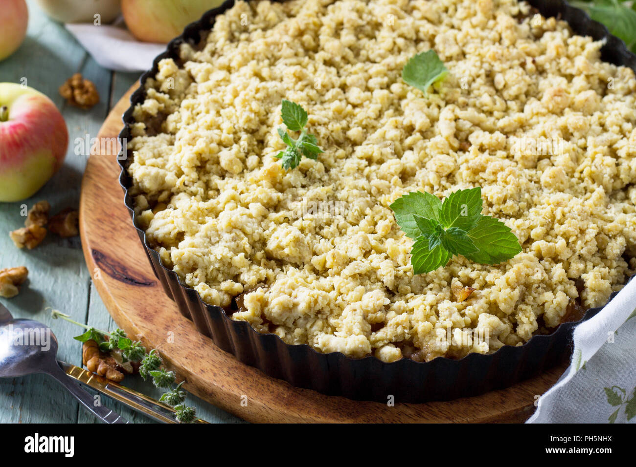Traditional English cuisine. Apples crumble, crisp in baking dish on wooden table. - Stock Image