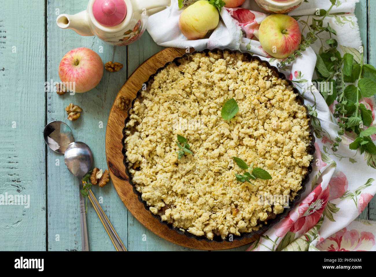 Traditional English cuisine. Apples crumble, crisp in baking dish on wooden table. Top view flat lay background. - Stock Image