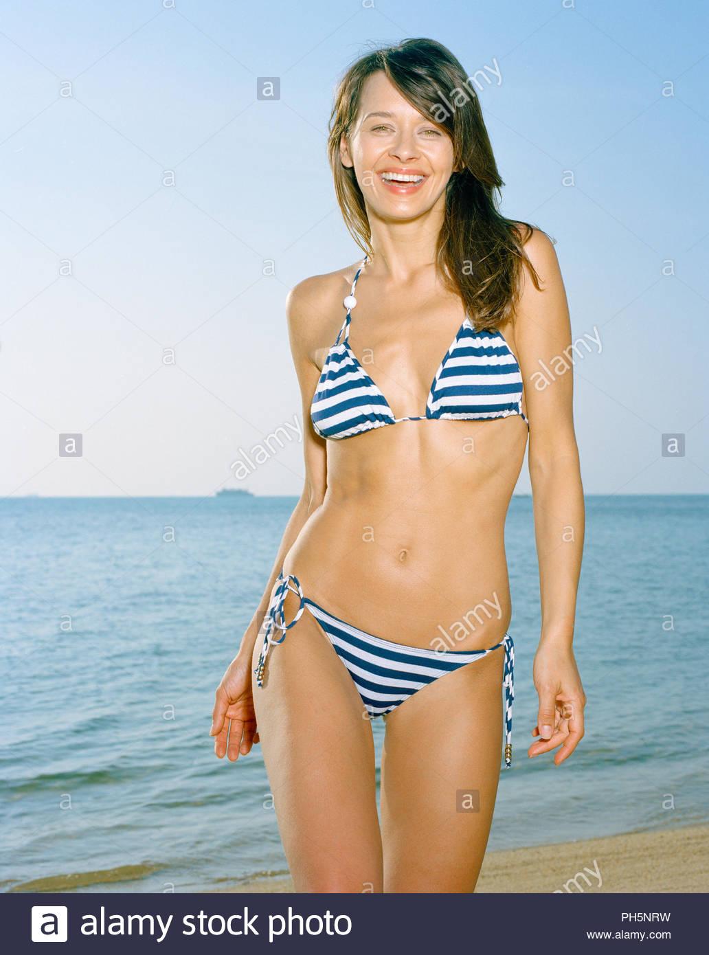 Young woman wearing striped bikini on beach - Stock Image