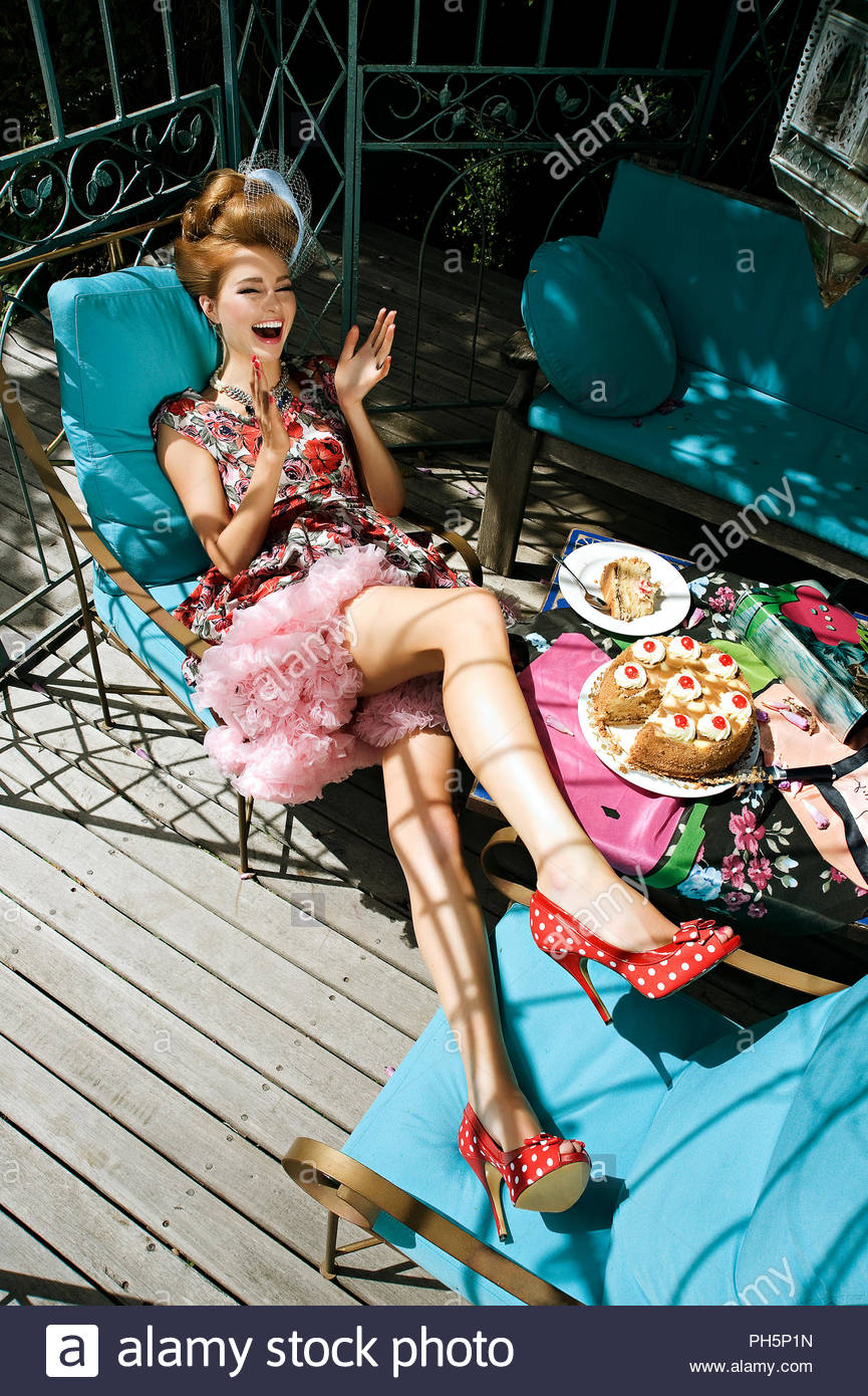 Young woman laughing in outdoor chair - Stock Image