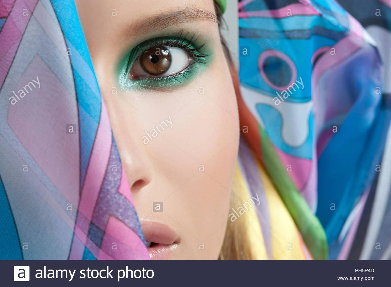 Young woman wearing green eyeshadow - Stock Image