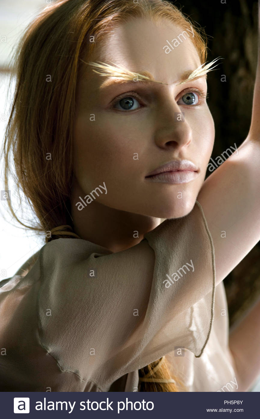 Young woman with feather eyebrows - Stock Image
