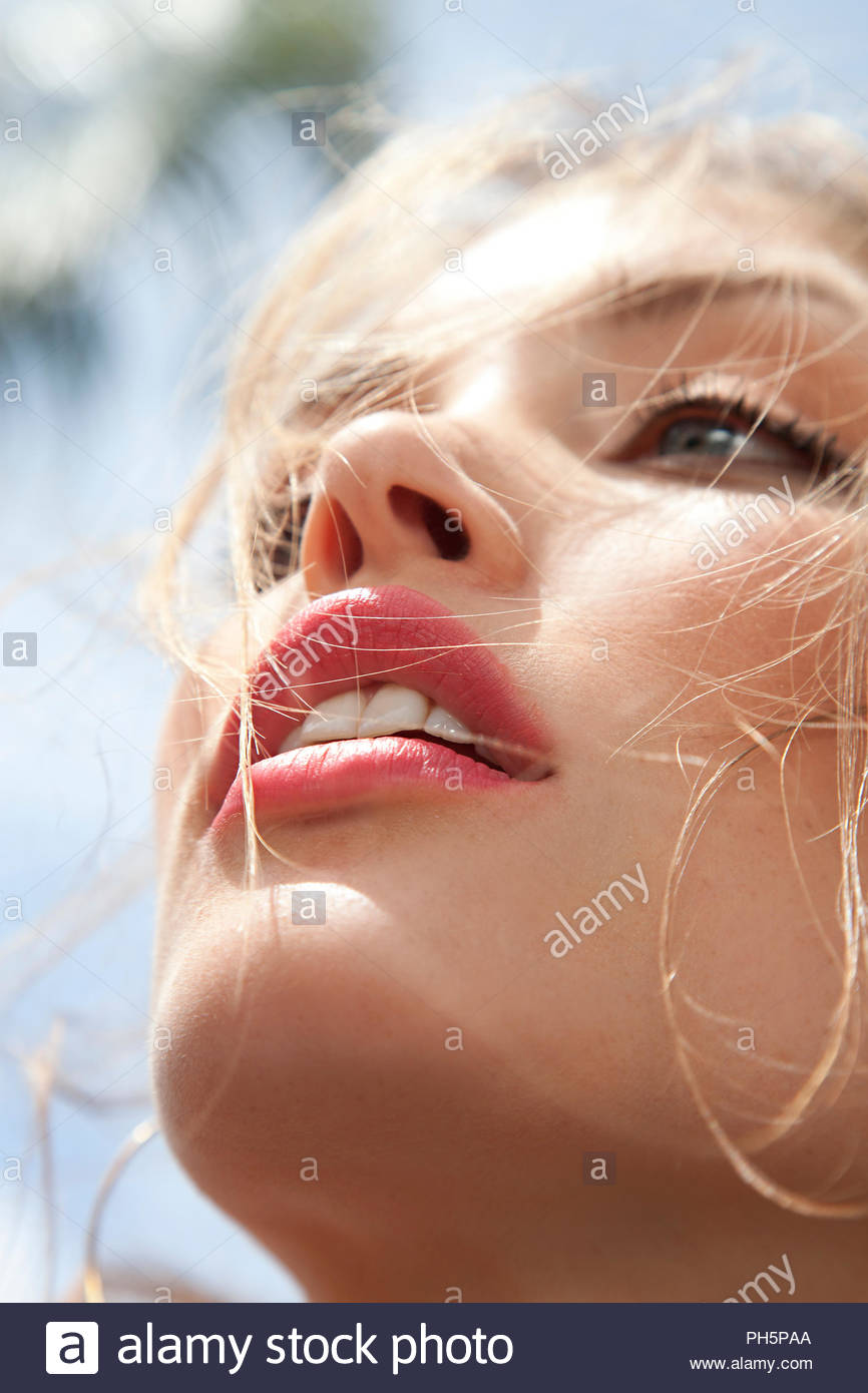 Close up of young woman wearing red lipstick - Stock Image