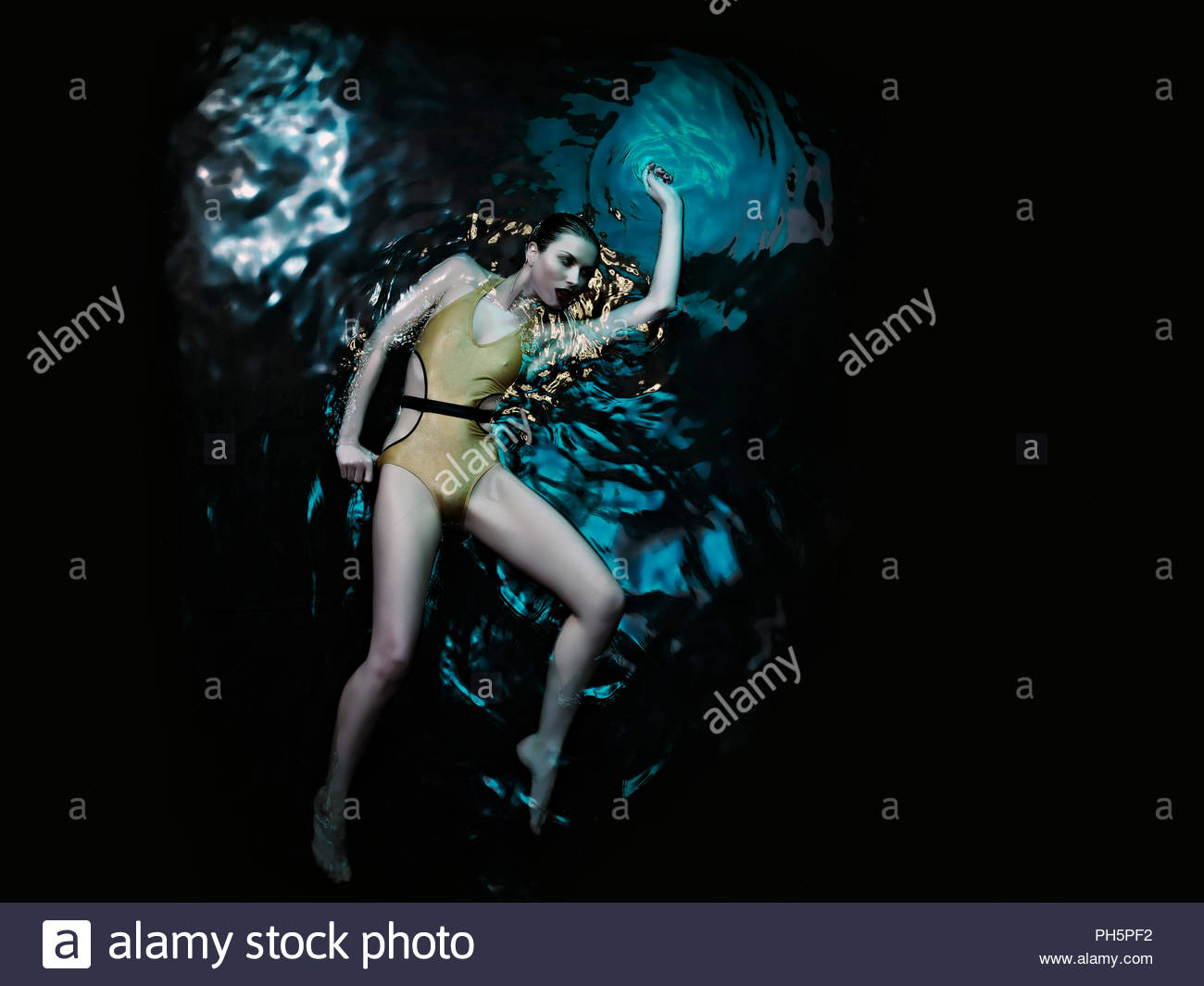 Young woman in swimsuit lying in water - Stock Image