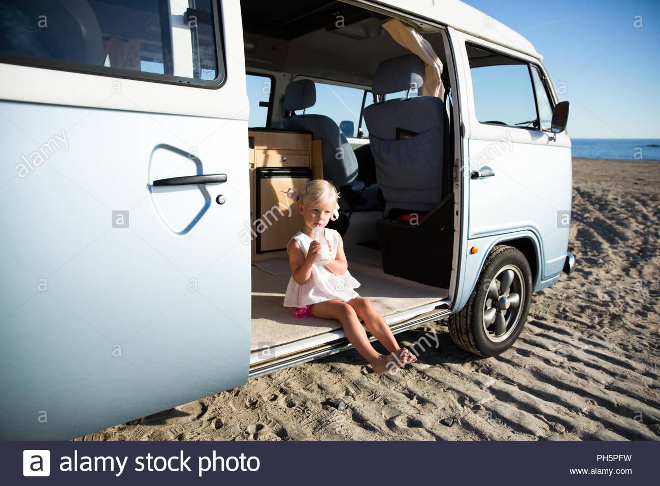 Girl drinking milk in van at beach - Stock Image