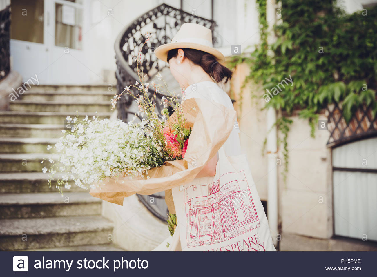 Young woman with bouquet of flowers by stone steps - Stock Image