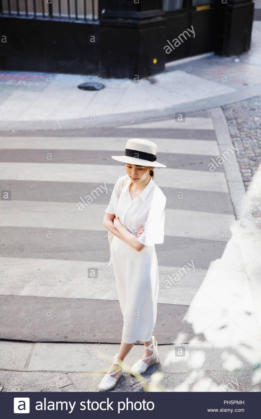 Young woman in sunhat with arms crossed on zebra crossing - Stock Image