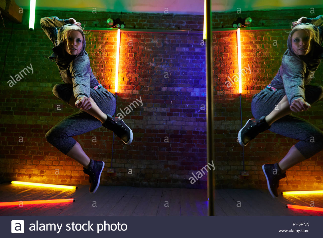 Young woman jumping by a mirror Stock Photo