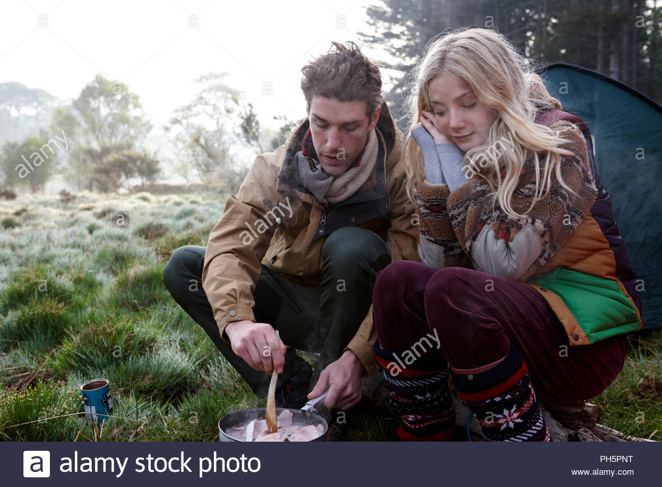 Couple cooking while camping - Stock Image