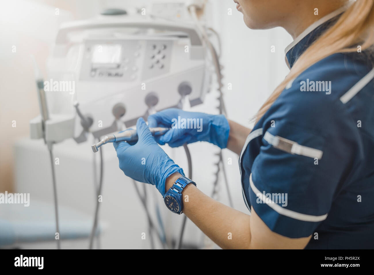Close up of woman dentist in blue uniform checking dental equipment. - Stock Image