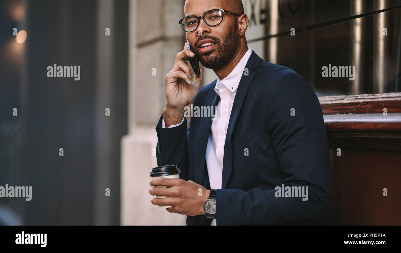 Portrait of handsome young businessman making a phone call while sitting outdoors with a coffee. Man in business suit talking over cell phone. - Stock Image
