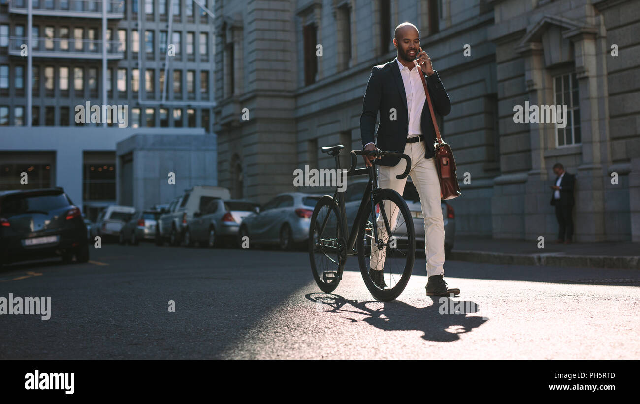Young businessman walking outdoors with a bicycle and using mobile phone. African man going to work on bike talking over cell phone on city street. - Stock Image