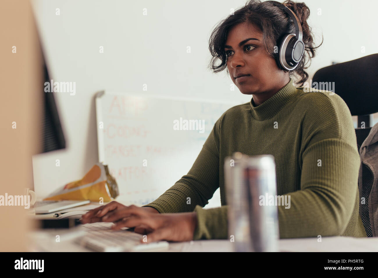 Female programmer working in a software developing company office. Woman wearing headphones coding on desktop computer. Stock Photo