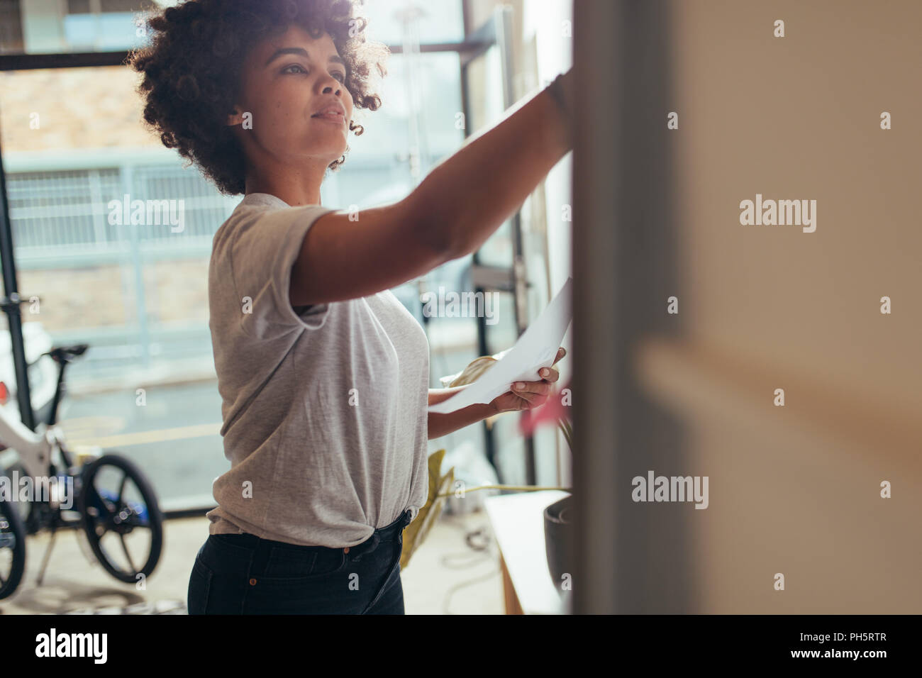 Businesswoman writing on whiteboard at meeting. Young african female working at tech startup writing new project plan on board. - Stock Image