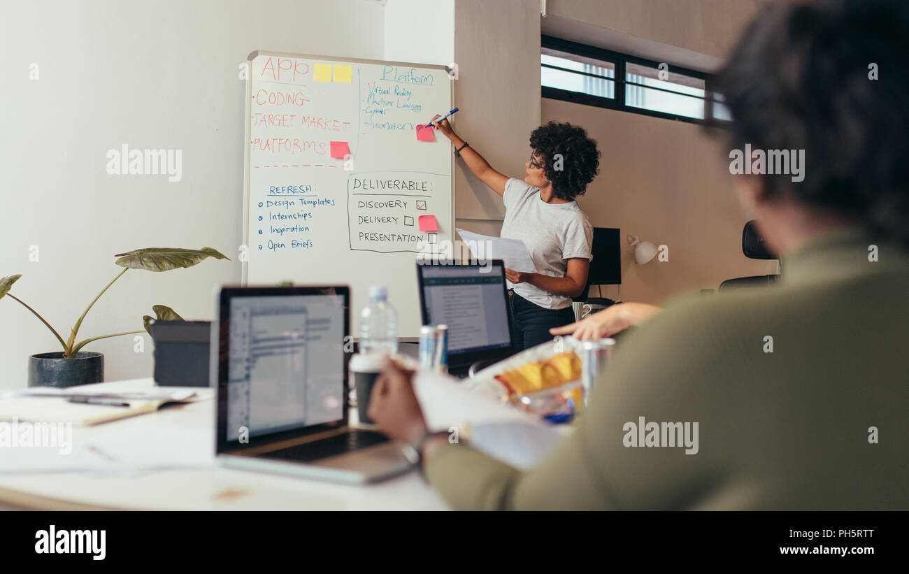 Team leader discussing and brainstorming new approaches and ideas with colleagues over new project. Business presentation at software development comp - Stock Image