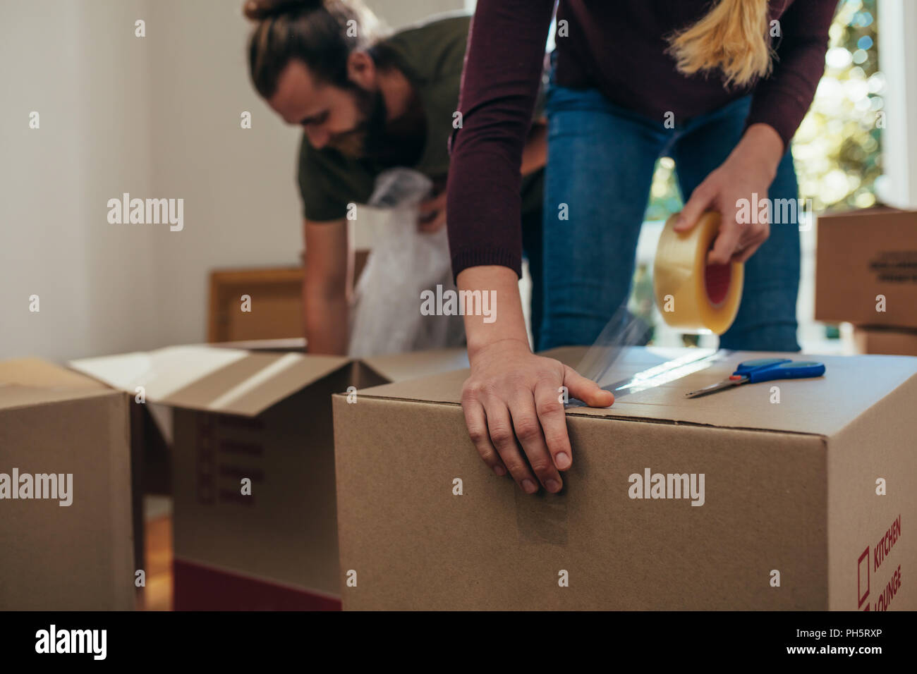 couple using packing boxes to pack their household items man