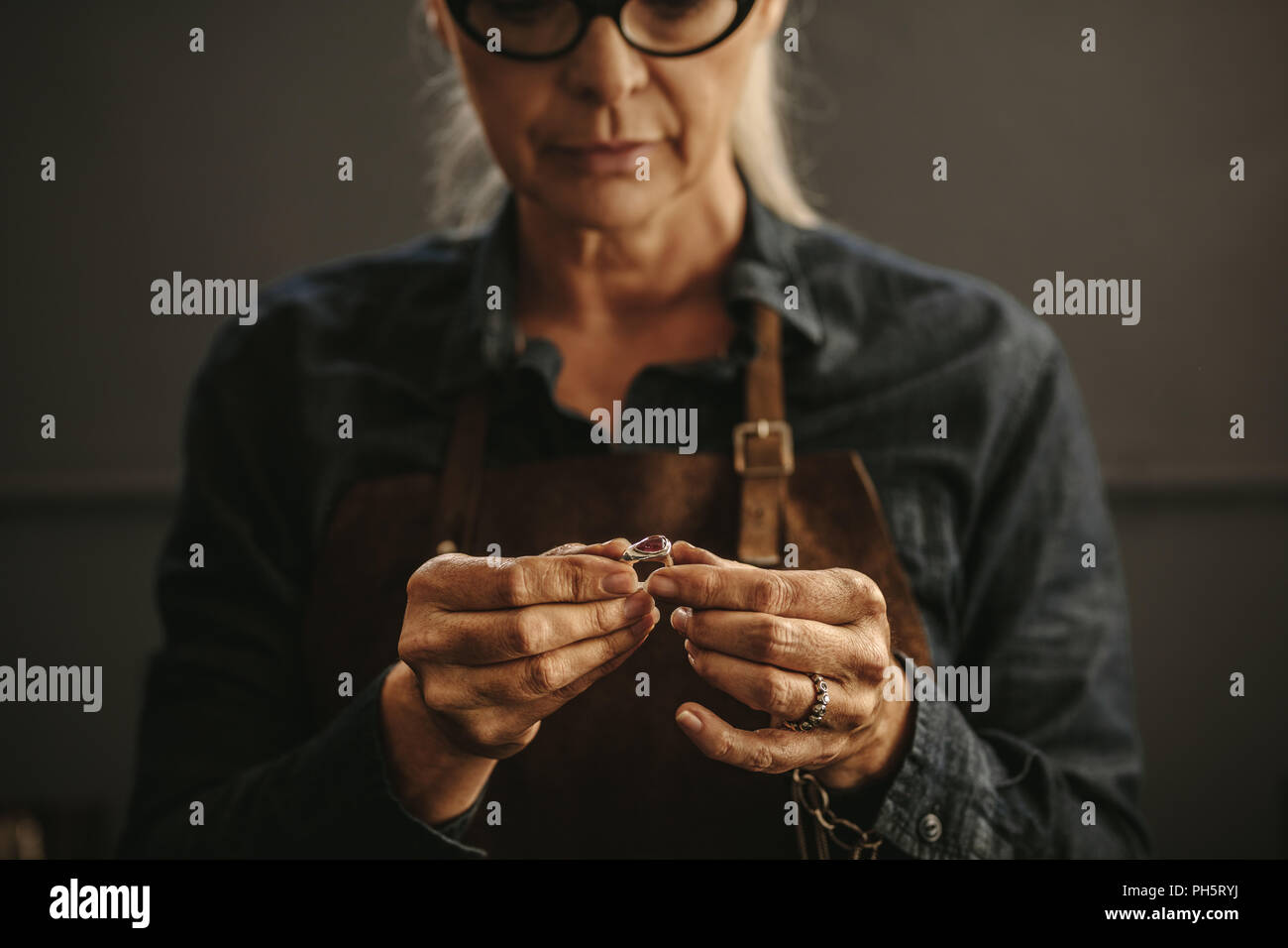 Close up of female jeweler hands examining the silver ring at workshop. Woman goldsmith inspecting jewelry. Stock Photo