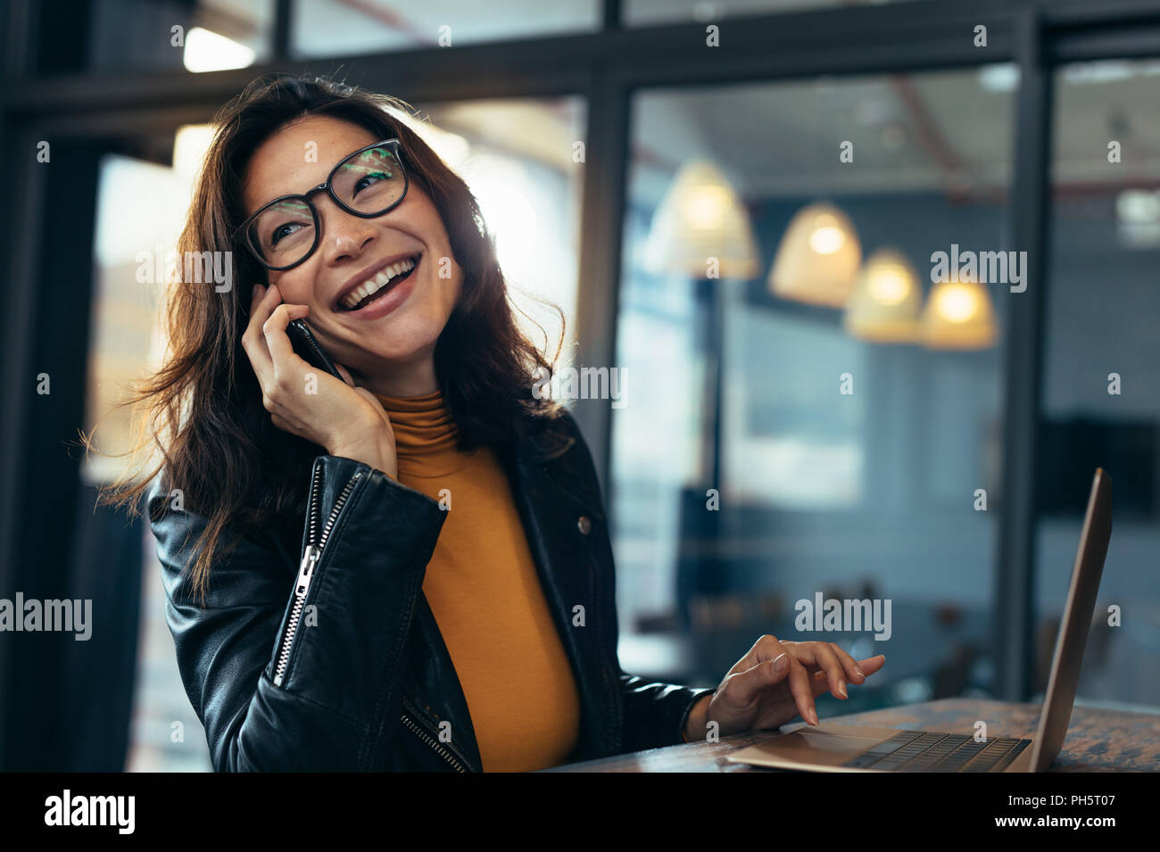 Cheerful asian female talking on mobile phone while sitting on desk with laptop. Business woman in casuals making a phone call and laughing. - Stock Image