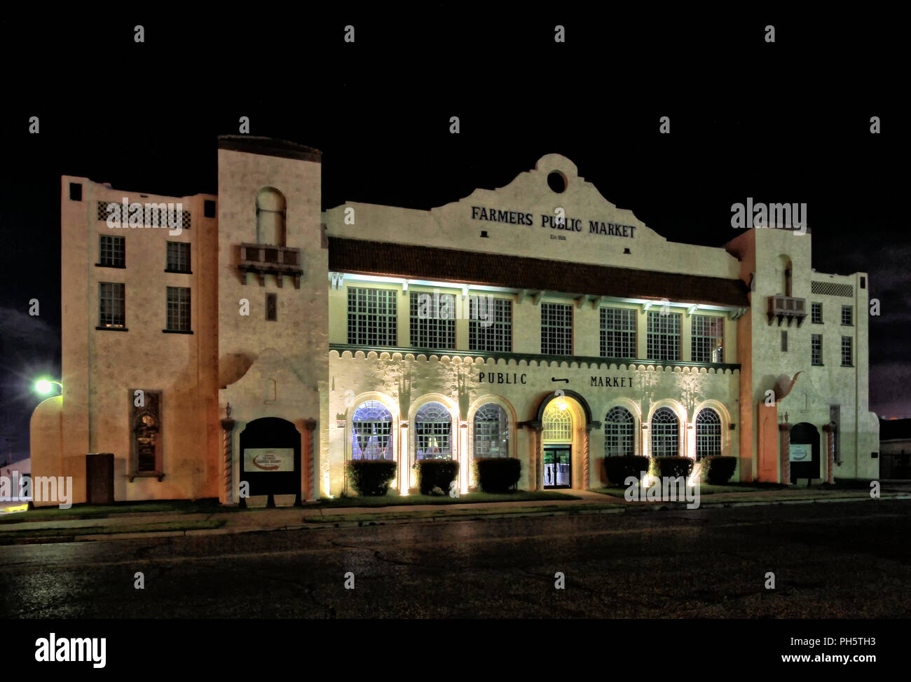 The historic Oklahoma City Farmers Public Market building is lit up at night. Stock Photo