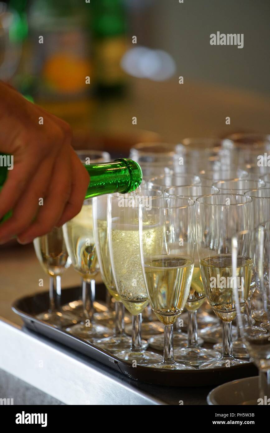 hand holding a bottle of sparkling wine, pouring in champagne cups - Stock Image