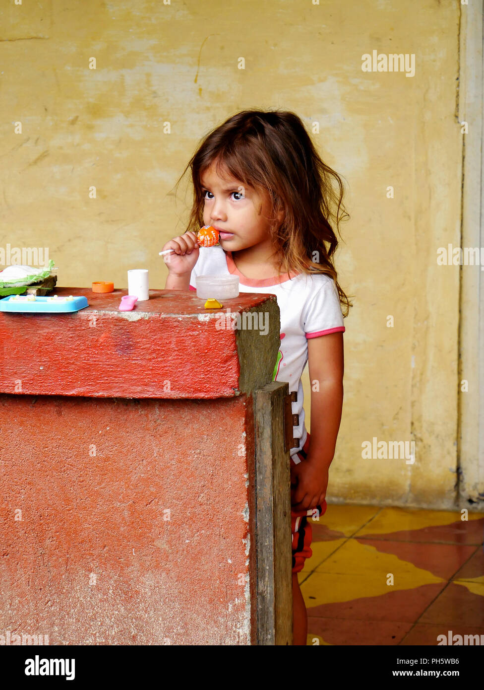 little poor girl eating an unopened lollipop in her house during a catholic mission in holy week - Stock Image