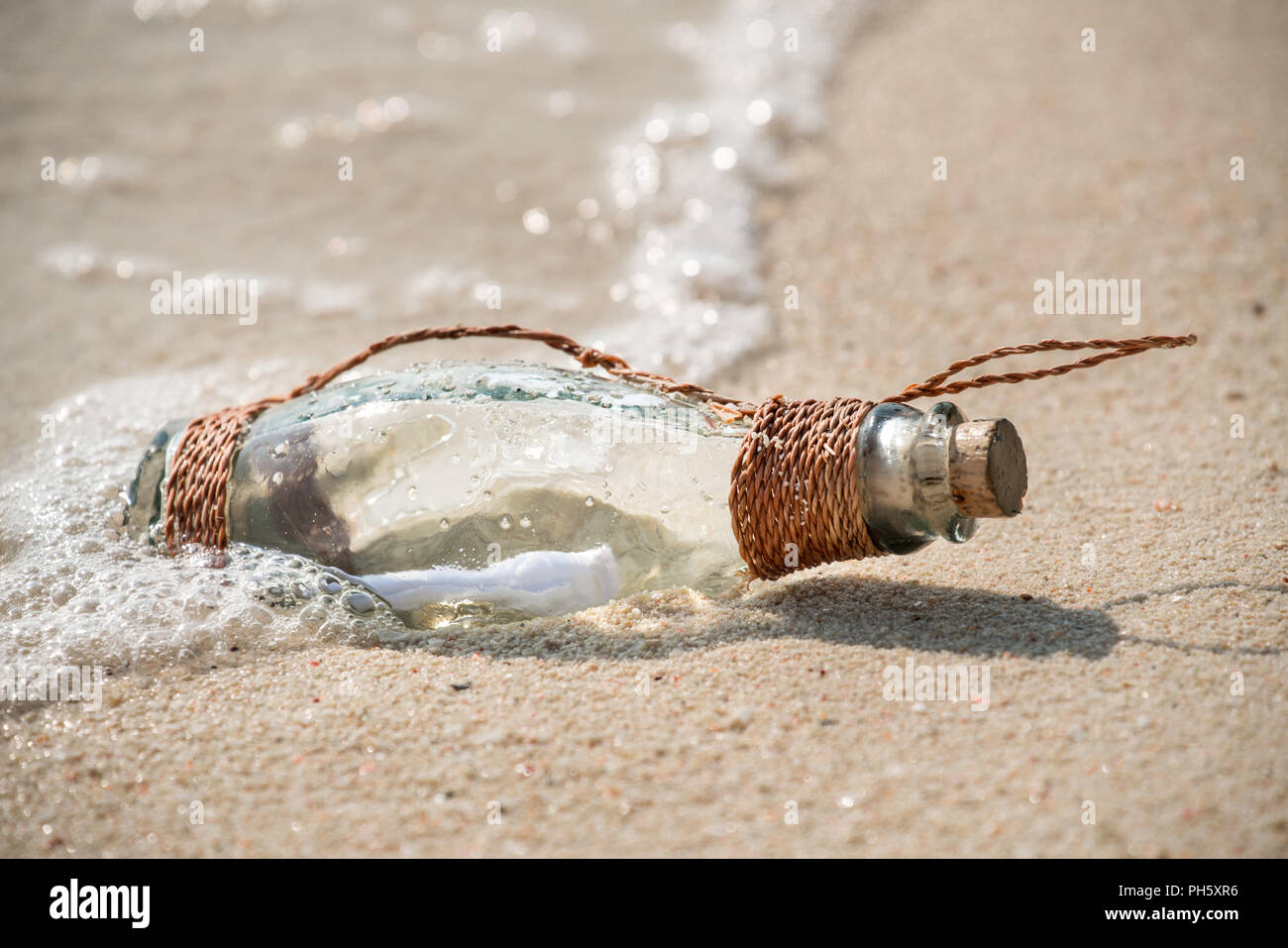 Letter message in a glass transparent bottle on the beach , concept for communication. - Stock Image