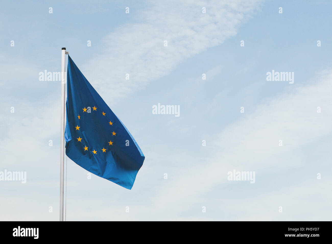 Flag of the European Union on the flagpole against the sky. - Stock Image
