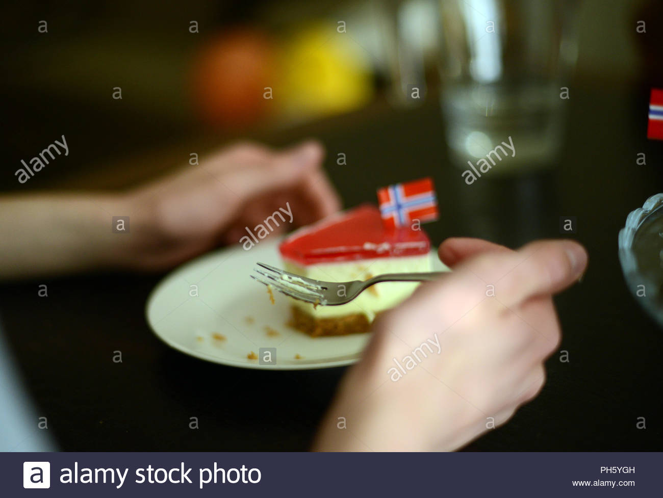 eating cheese cake, decorated with norwegian flags on a Norwegian national day 17 may - Stock Image