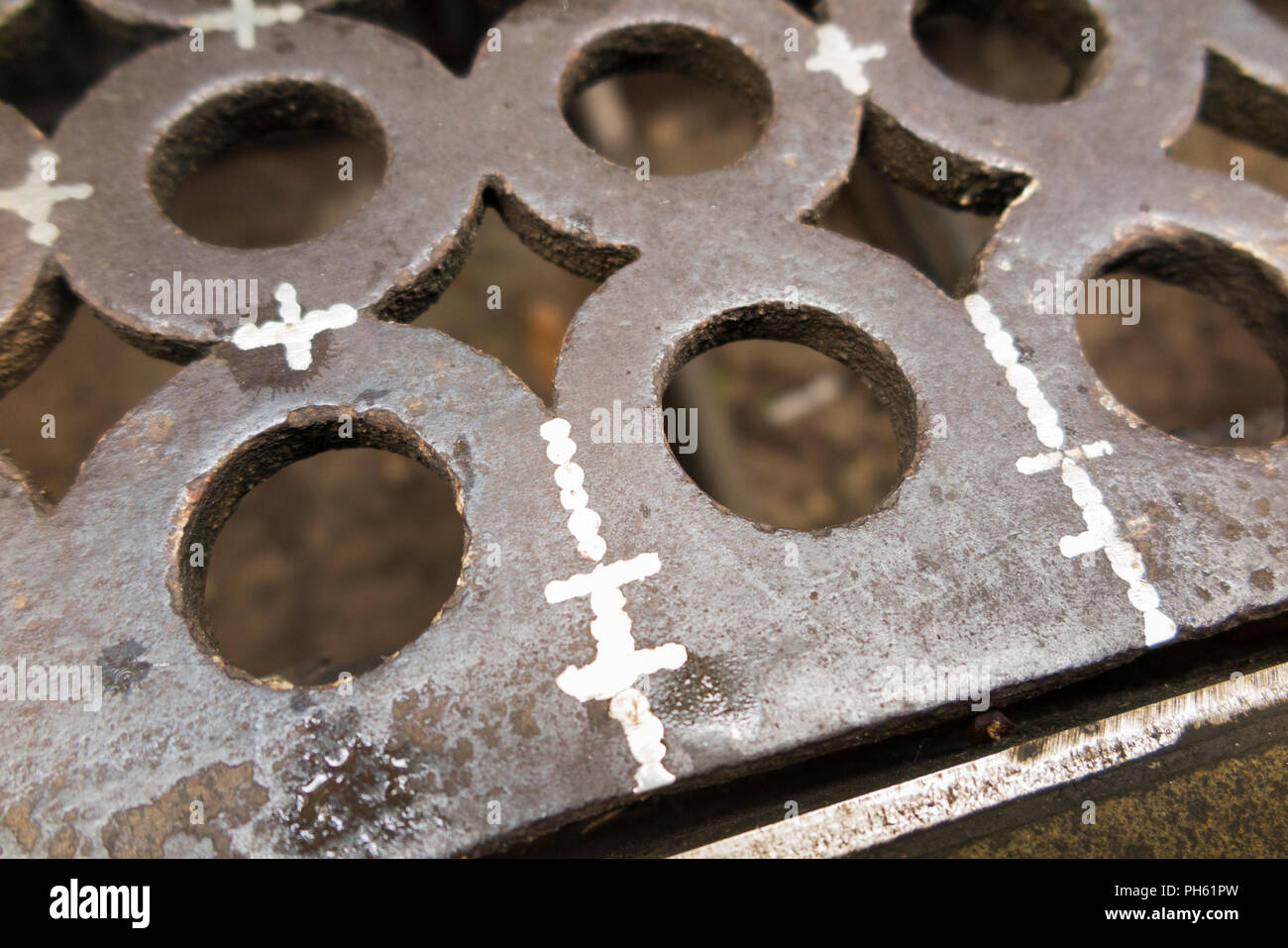 An iron Victorian era drain grill which has cracks / has cracked and been repaired with a weld / been welded. UK. (101) - Stock Image