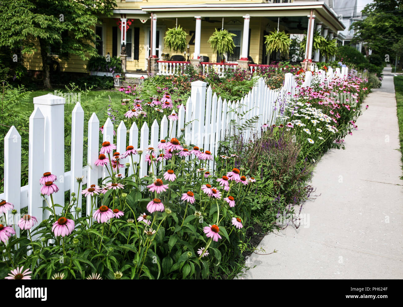 White picket fence with a flower border and victorian house in white picket fence with a flower border and victorian house in babkground mercer county new jersey usa united states mightylinksfo