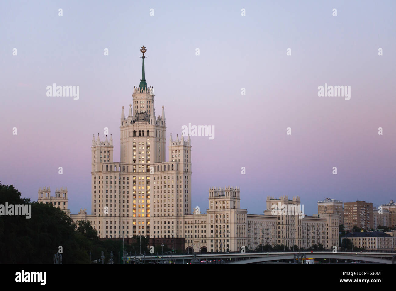 Kotelnicheskaya Embankment Building pictured at sunset from the Floating Bridge in Zaryadye Park in Moscow, Russia. One of the seven Stalinist skyscrapers was designed by Soviet architects Dmitry Chechulin and Andrei Rostkovsky and built in 1947-1952. - Stock Image