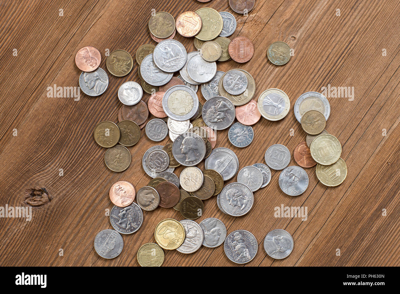 Coins on old wooden surface copyspace ready for edit as money themed cover - Stock Image