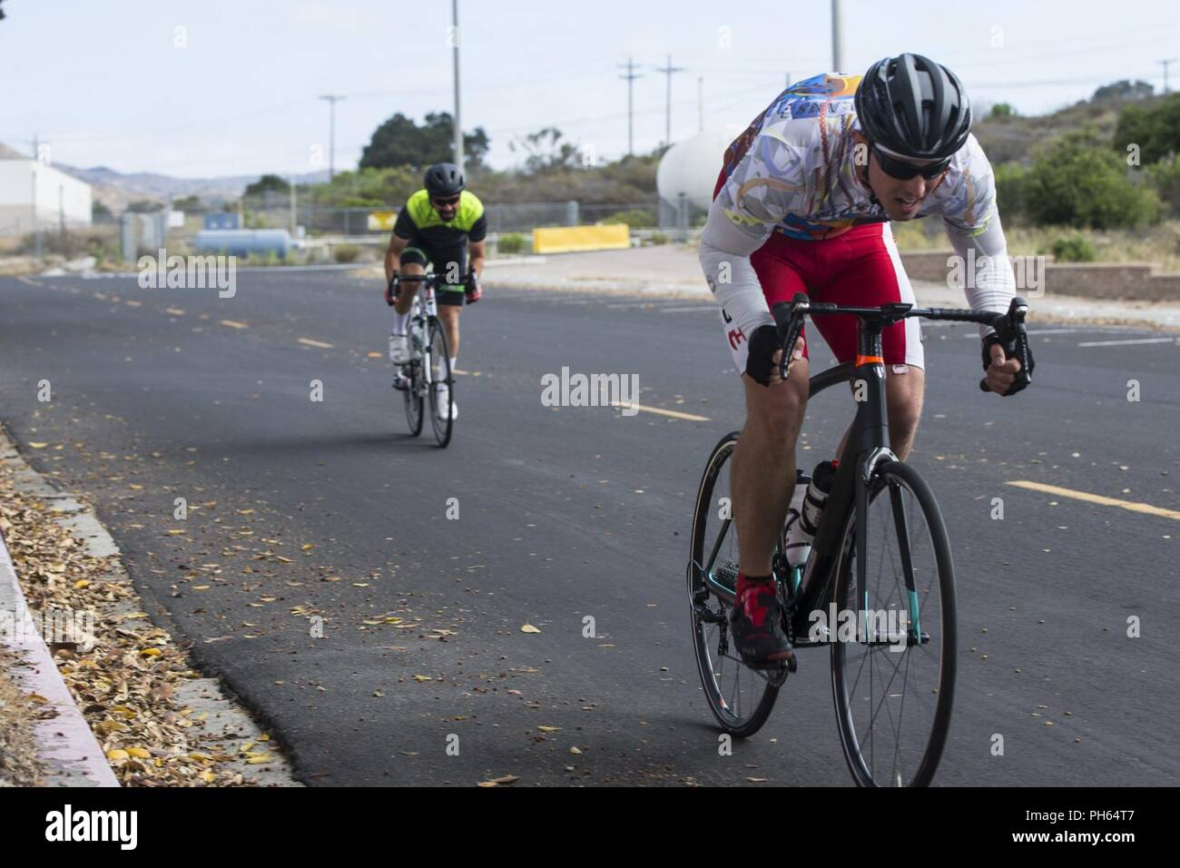 U.S. Marine Corps Staff Sgt. James Dunaway, right, infantry unit leader, Wounded Warrior Battalion-West, and retired Master Sgt. Mark Mann, left, volunteer, perform timed trials at Marine Corps Base Camp Pendleton, California, June 26, 2018. Dunaway and his coaches haved trained several months cycling over 30 miles a day, five days a week. - Stock Image