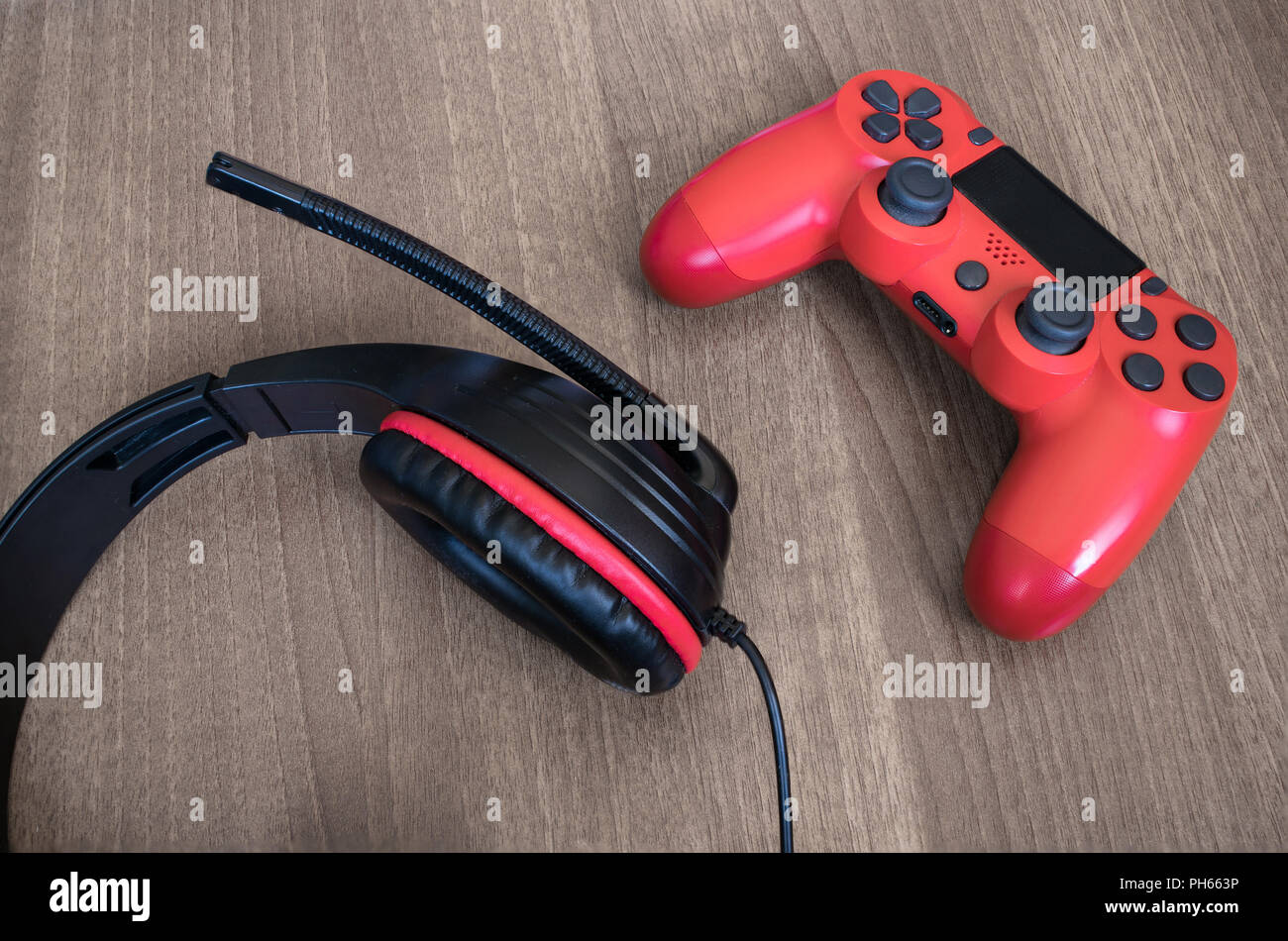 Headset and red video game controller. - Stock Image