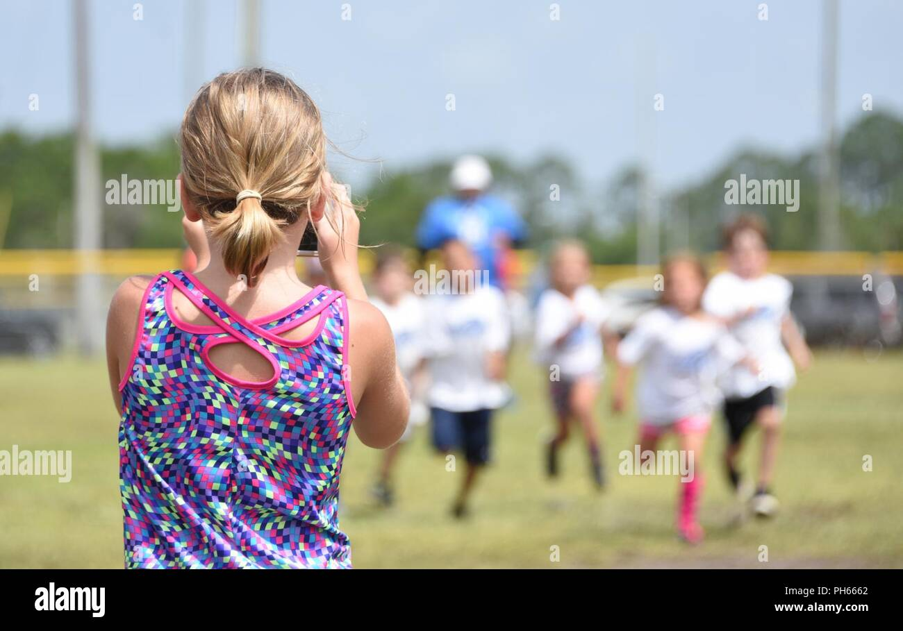 A child films participants of the LeGarrette Blount Pro Camp during a race to find out the fastest camper from the Tyndall Youth Center at Tyndall Air Force Base, Fla., June 22, 2018. The winners of the race received an autographed 8x10 photo of Blount and a photo with the Detroit Lions running back. - Stock Image