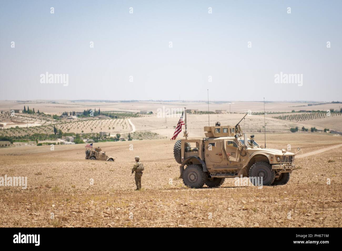U.S. Soldiers provide security during a coordinated, independent patrol along the demarcation line in a village near Manbij, Syria, June 26, 2018. Turkish military and Coalition Forces recently began patrolling on each side of the line to ensure the safety and stability of the region. Stock Photo