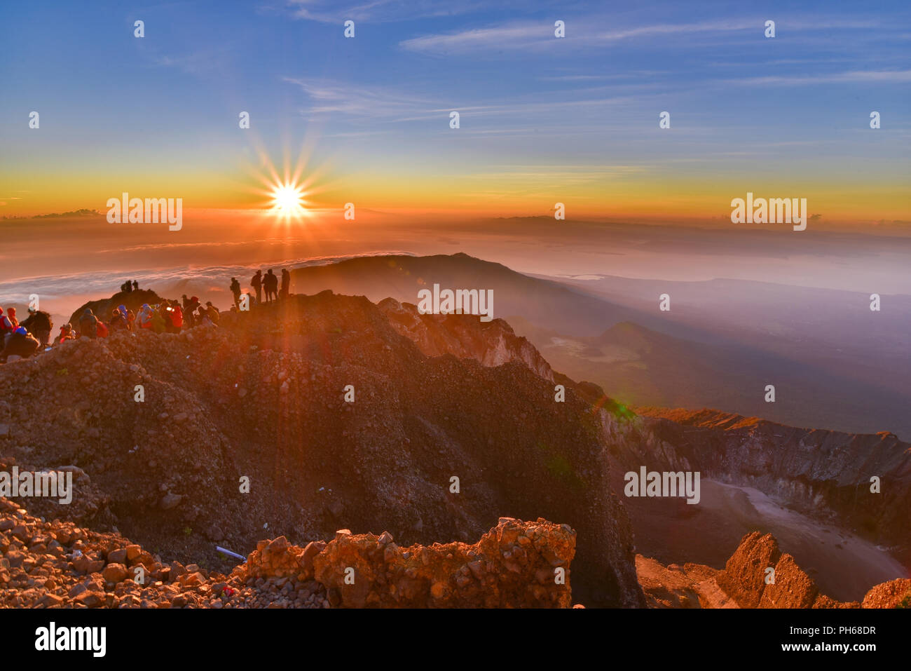People on the summit of volcano Rinjani watching sunrise, Lombok, Indonesia - Stock Image