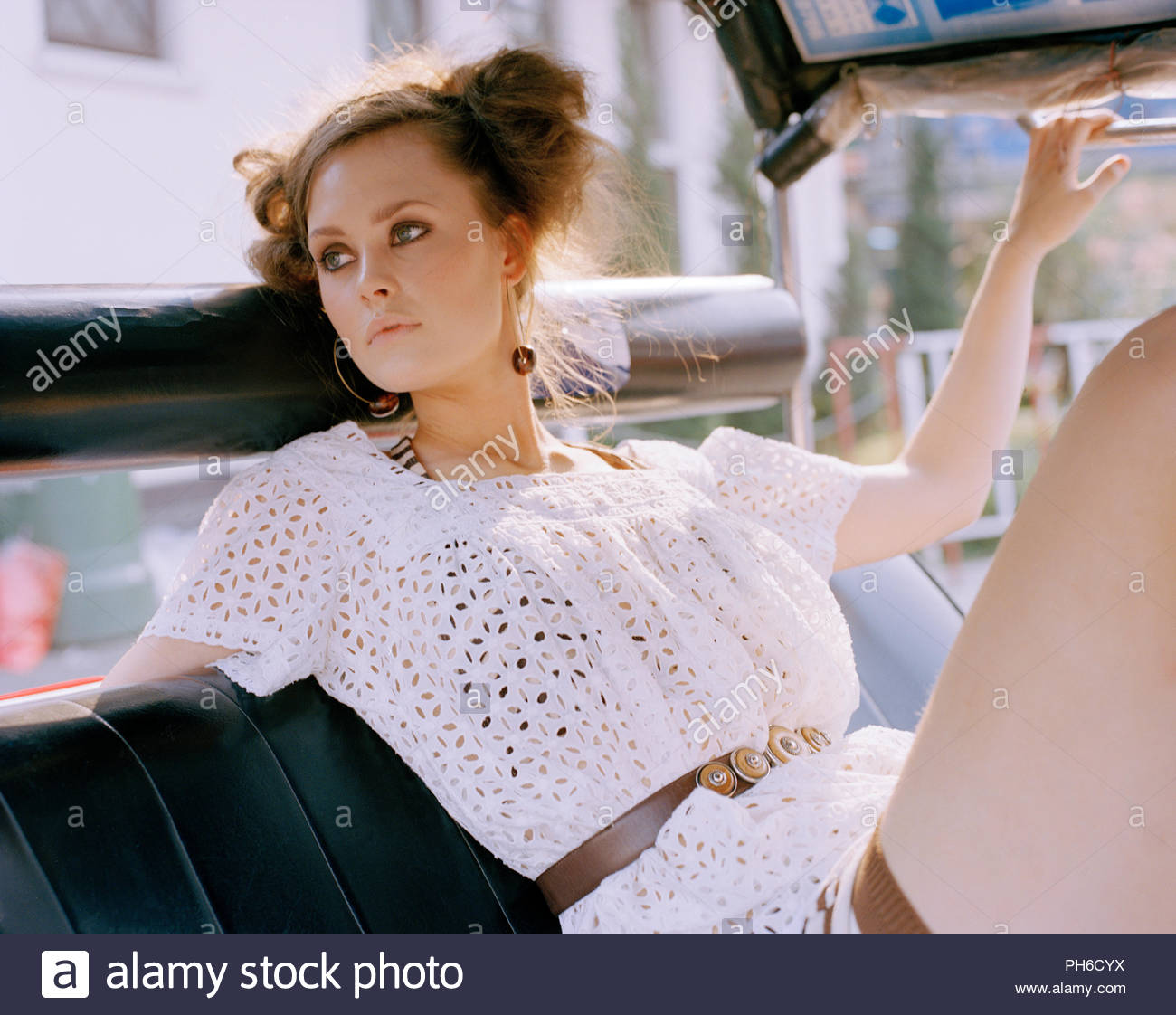 Young woman wearing white blouse with belt - Stock Image