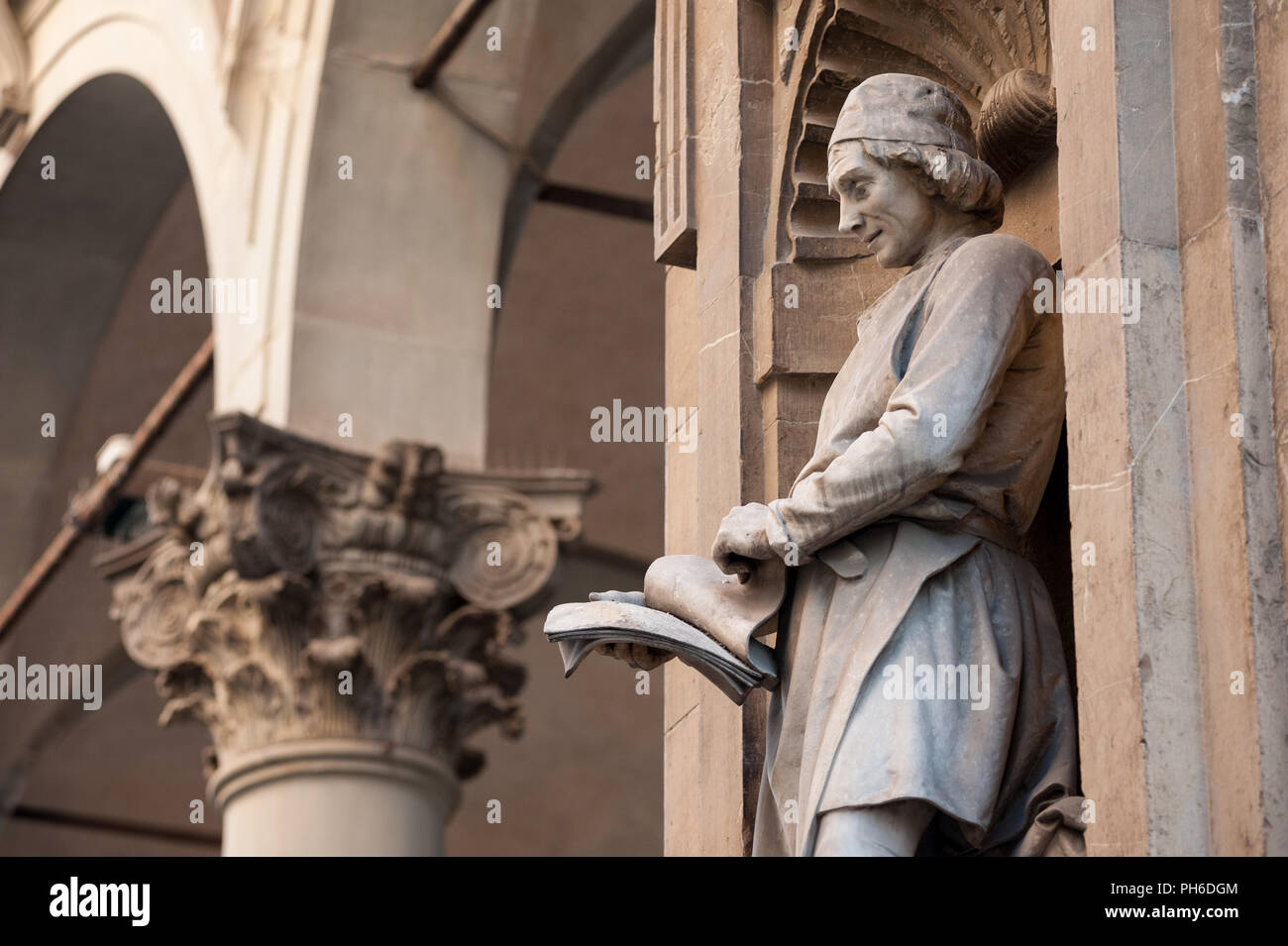 Bernardo Cennini scans printing proofs in a niche overlooking the Mercato Nuovo, Florence, Italy - Stock Image