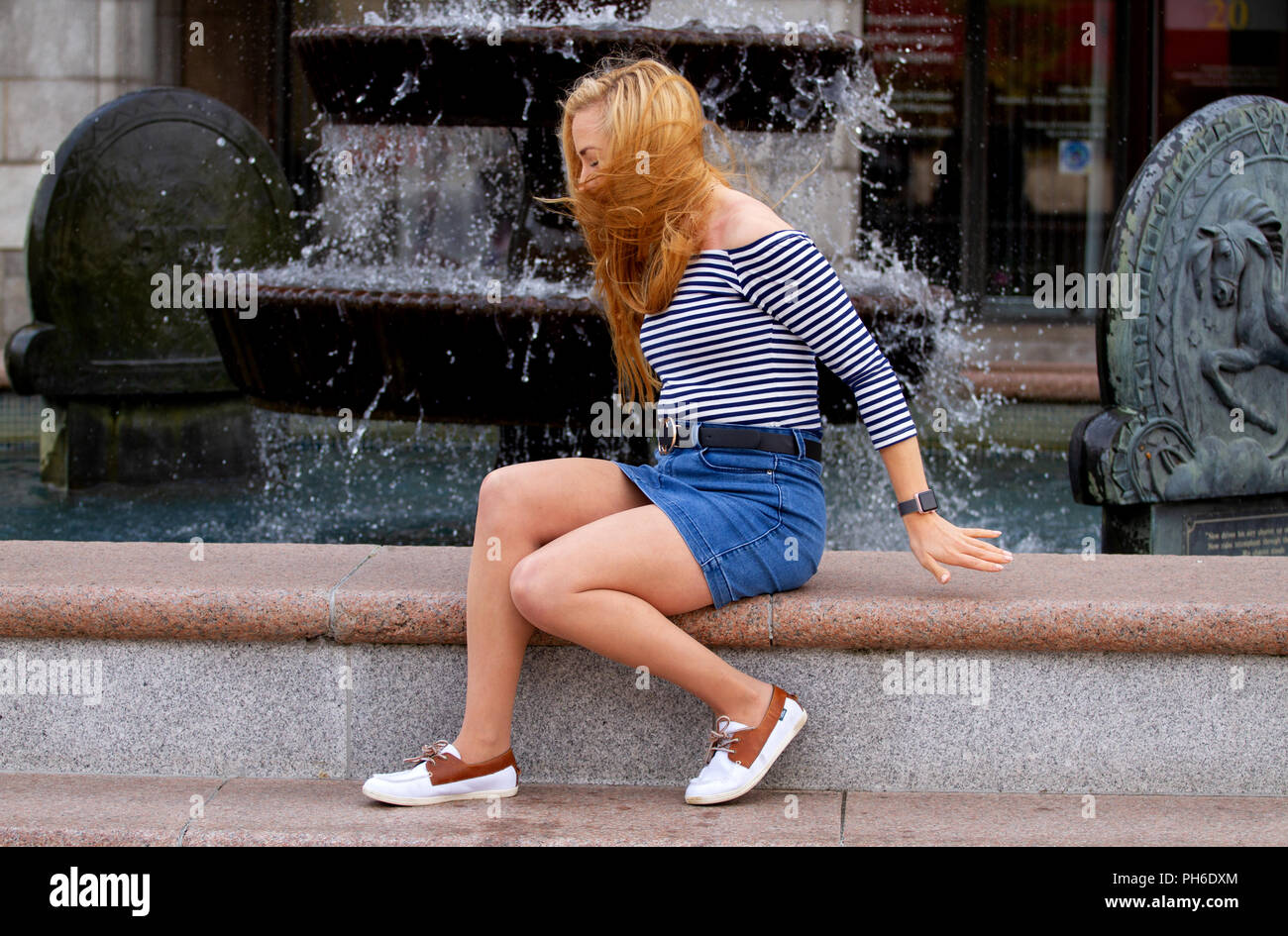 A young woman with long blond hair blowing across her face while sitting beside a fountain at the City Square in Dundee, UK - Stock Image