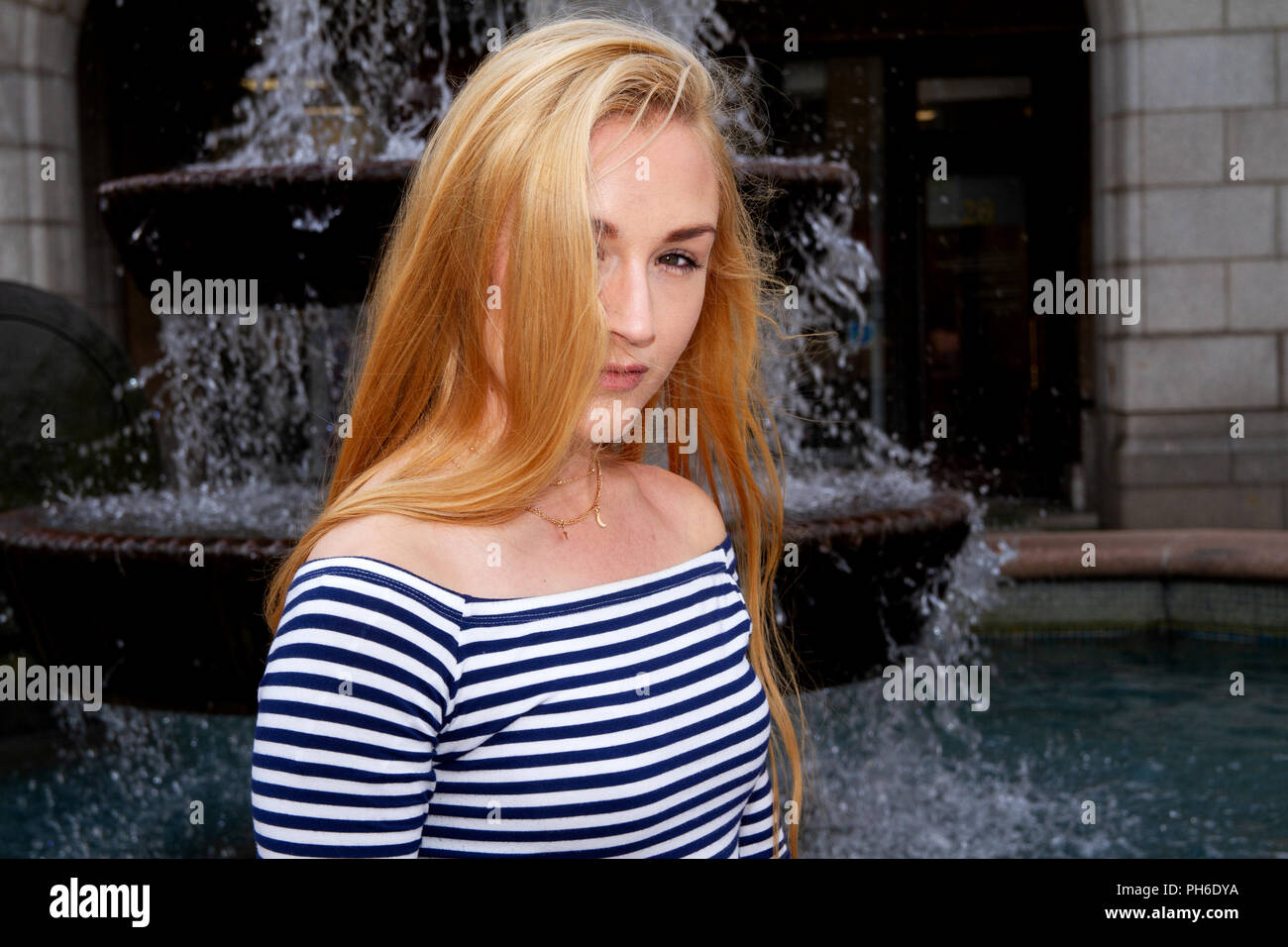 Close up of a  young woman with long blond hair sitting beside a fountain on a breezy day at the City Square in Dundee, UK - Stock Image