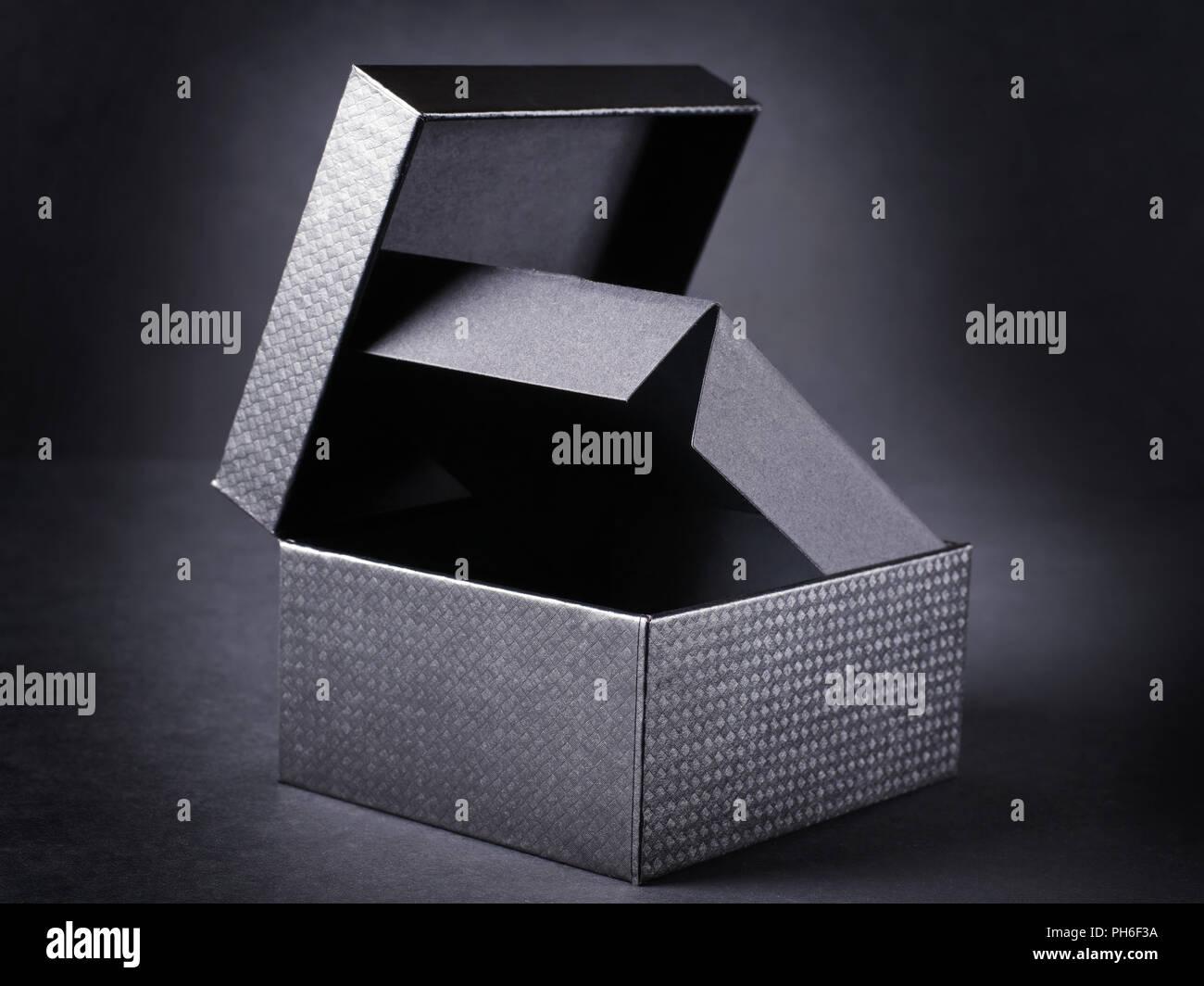 Open black box on black background. - Stock Image