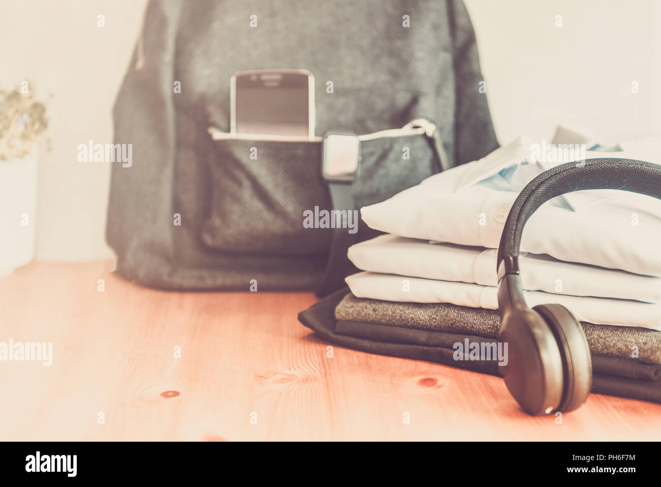 Back to school concept, backpack with school uniform such as white shirts and sweater, as well as electronic devices such as smart watch, mobile phone Stock Photo