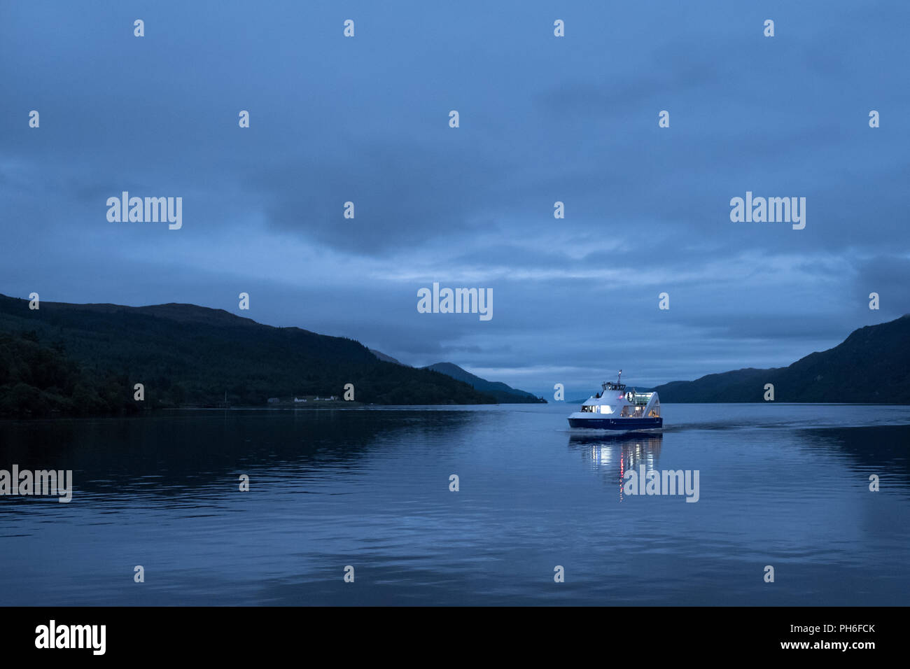 Loch Ness, central Highlands of Scotland. Boat on the water at twilight. Photographed at Fort Augustus. - Stock Image