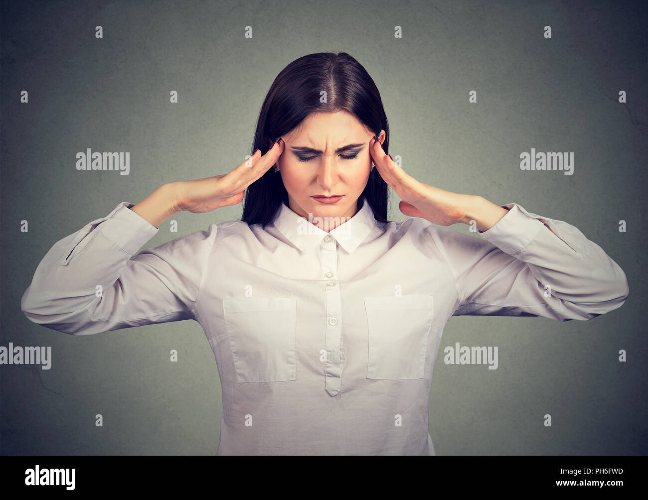 Woman holding fingers on temples trying to concentrate on decision making looking stressed - Stock Image